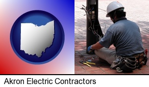 an electrician wearing a tool belt, installing electrical wiring in Akron, OH