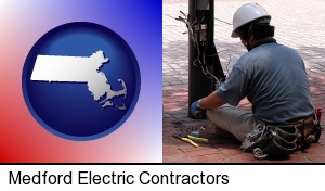 an electrician wearing a tool belt, installing electrical wiring in Medford, MA