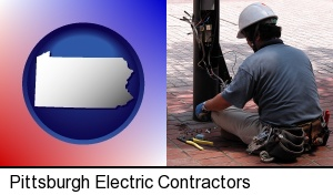 Pittsburgh, Pennsylvania - an electrician wearing a tool belt, installing electrical wiring