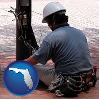 florida an electrician wearing a tool belt, installing electrical wiring