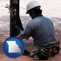 missouri an electrician wearing a tool belt, installing electrical wiring