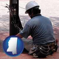 mississippi an electrician wearing a tool belt, installing electrical wiring