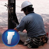 vermont an electrician wearing a tool belt, installing electrical wiring