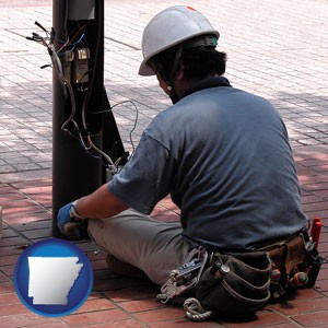 an electrician wearing a tool belt, installing electrical wiring - with Arkansas icon