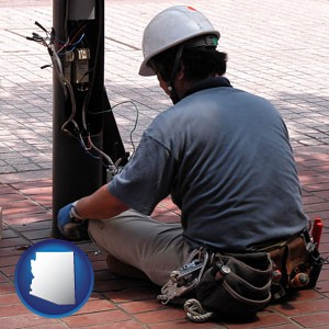 an electrician wearing a tool belt, installing electrical wiring - with Arizona icon
