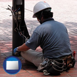 an electrician wearing a tool belt, installing electrical wiring - with Colorado icon