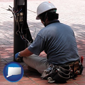 an electrician wearing a tool belt, installing electrical wiring - with Connecticut icon