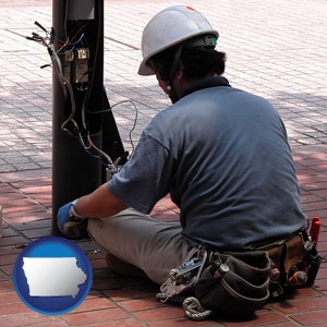 an electrician wearing a tool belt, installing electrical wiring - with Iowa icon