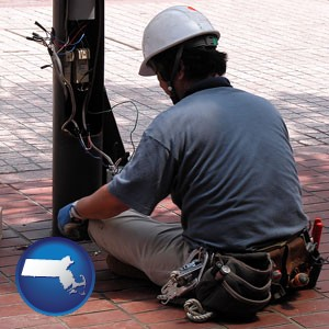 an electrician wearing a tool belt, installing electrical wiring - with Massachusetts icon