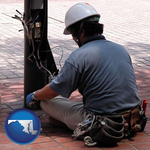 an electrician wearing a tool belt, installing electrical wiring - with Maryland icon
