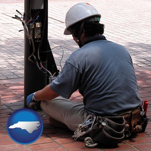 an electrician wearing a tool belt, installing electrical wiring - with North Carolina icon