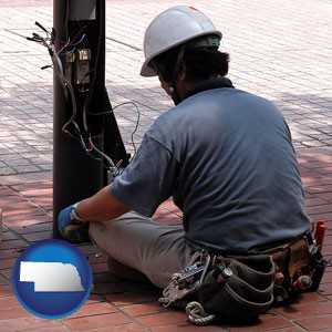 an electrician wearing a tool belt, installing electrical wiring - with Nebraska icon