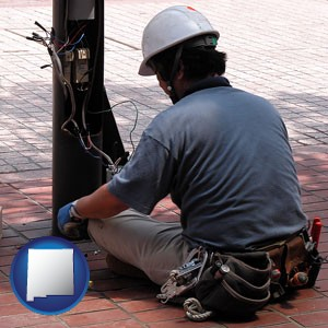 an electrician wearing a tool belt, installing electrical wiring - with New Mexico icon