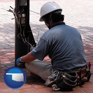an electrician wearing a tool belt, installing electrical wiring - with Oklahoma icon