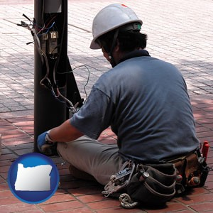 an electrician wearing a tool belt, installing electrical wiring - with Oregon icon