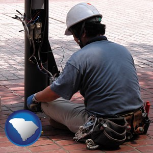 an electrician wearing a tool belt, installing electrical wiring - with South Carolina icon