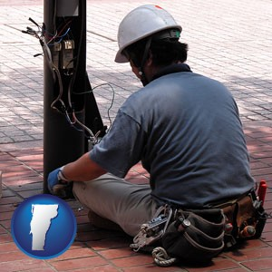 an electrician wearing a tool belt, installing electrical wiring - with Vermont icon