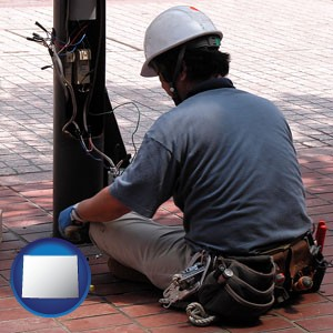 an electrician wearing a tool belt, installing electrical wiring - with Wyoming icon