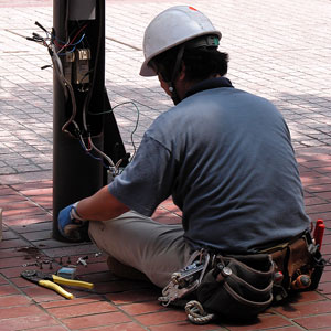 an electrician wearing a tool belt, installing electrical wiring